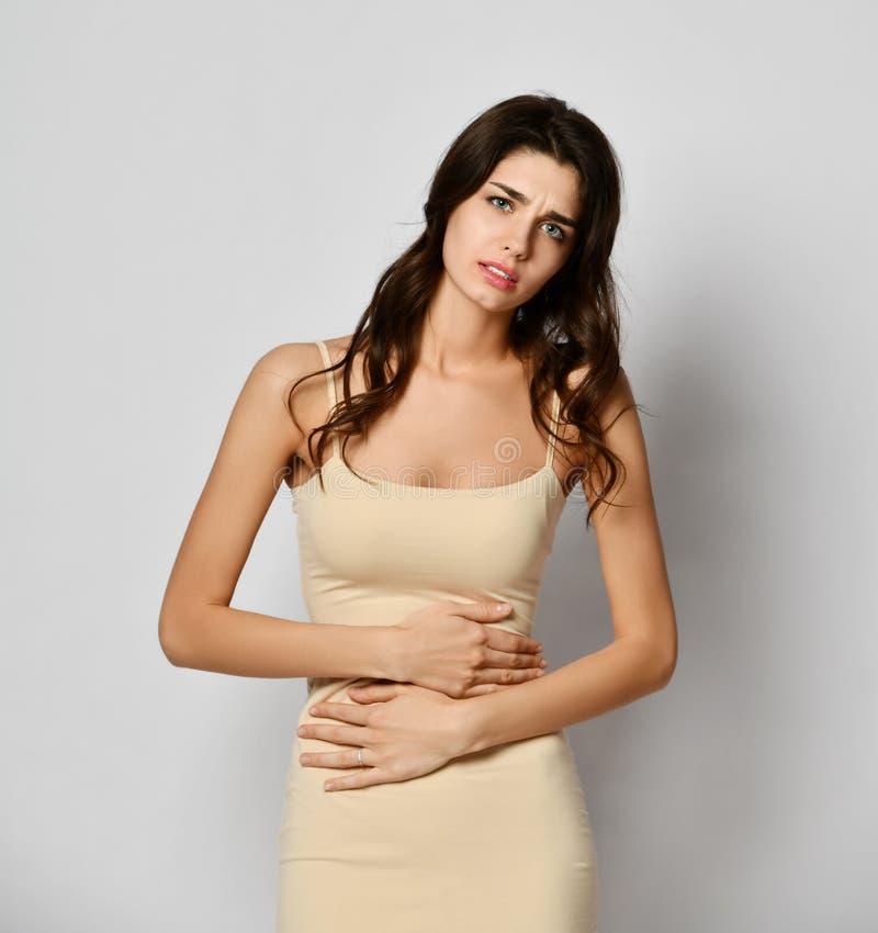 Sofrimento da jovem mulher da dor de estômago abdominal Menina preocupada que toca na barriga fotografia de stock royalty free