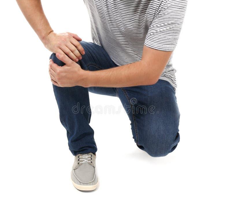 Sofrimento do homem da dor no joelho no fundo branco foto de stock