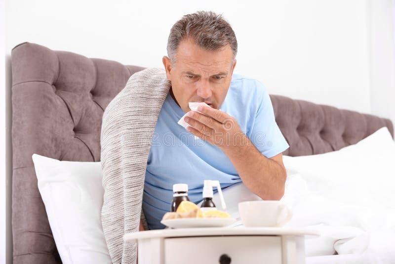 Sofrimento do homem da tosse e frio na cama foto de stock