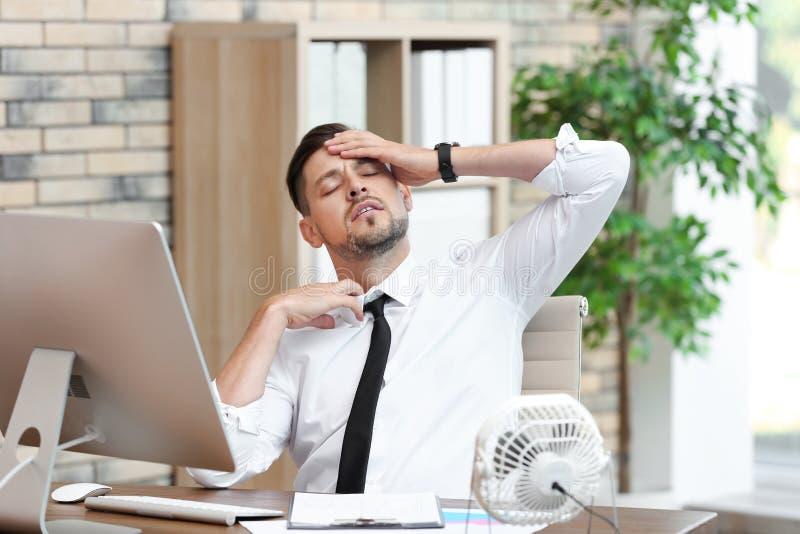 Sofrimento do homem de negócios do calor na frente do fã pequeno imagens de stock royalty free