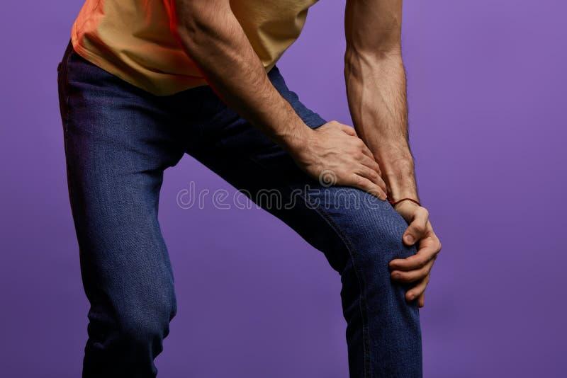 Sofrimento do homem novo da dor no fundo azul foto de stock