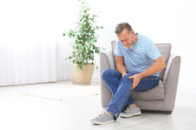 Sofrimento do homem superior da dor do joelho na sala de visitas imagens de stock