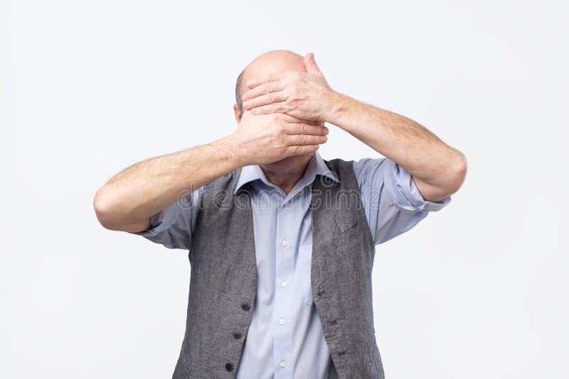Sofrimento do homem superior dos sentimentos dolorosos que griefing a cabeça de dobra abaixo de cobrir a cara com as palmas imagens de stock royalty free