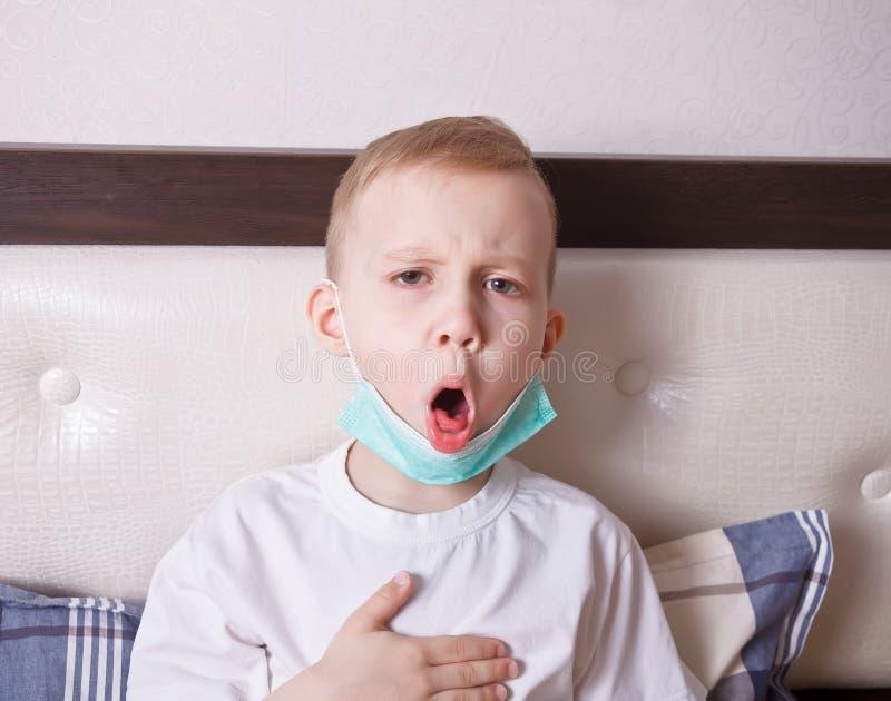 Sofrimento doente do menino da tosse na cama em casa imagens de stock