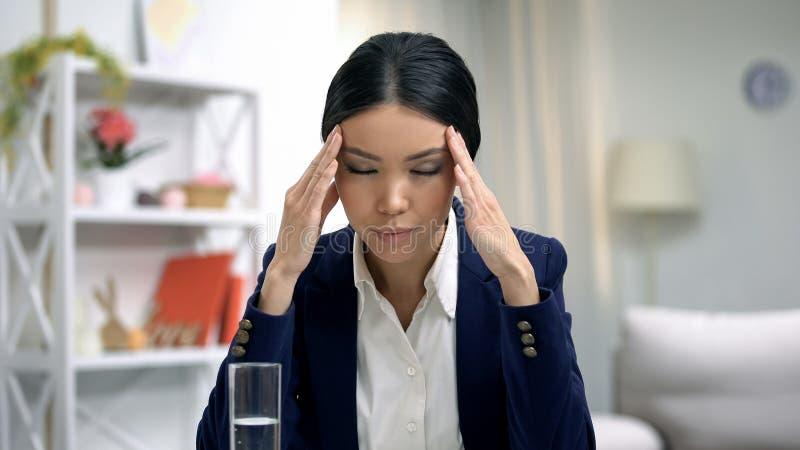 Sofrimento forçado do empregado da dor de cabeça, vidro de água na tabela, cuidados médicos fotografia de stock