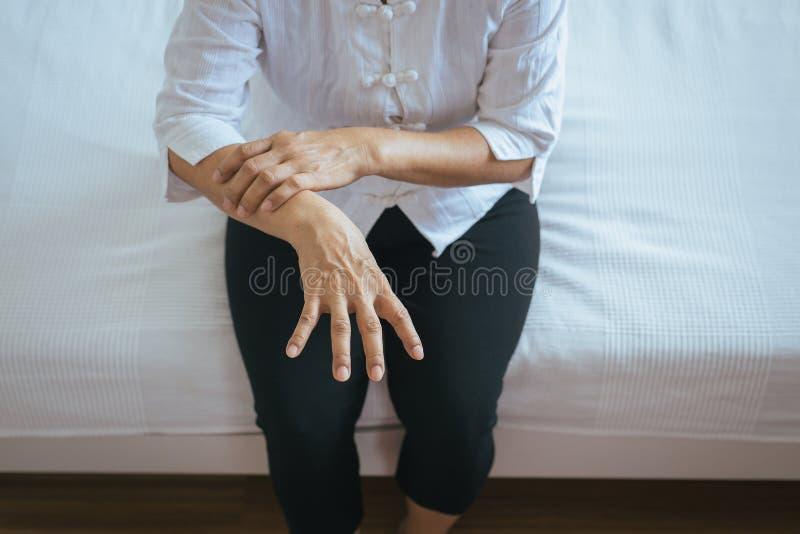 Sofrimento idoso da mulher com sintomas da doença de Parkinson fotos de stock royalty free