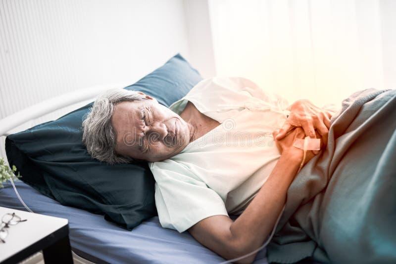 Sofrimento maduro do homem da dor de estômago Paciente superior na cama e estômago da dor na sala no hospital fotos de stock