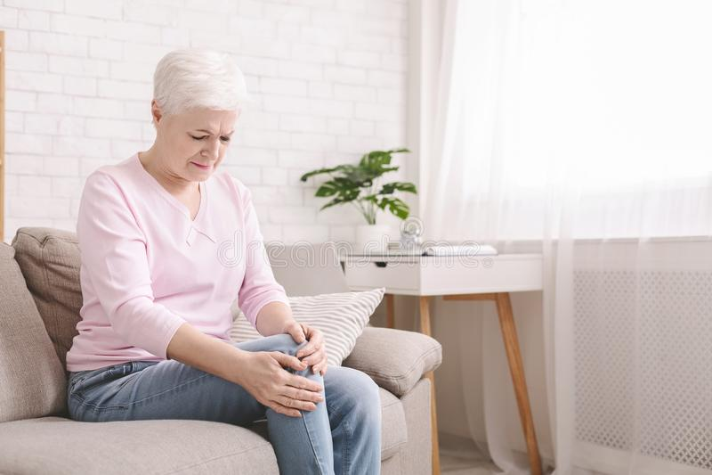 Sofrimento superior da mulher da dor no pé, fazendo massagens seu joelho fotos de stock