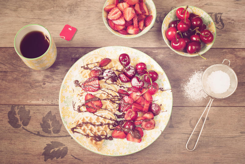 Soft Belgian heart shaped waffles with cherries and strawberries, chocolate topping and powdered sugar on yellow plate. Black royalty free stock image
