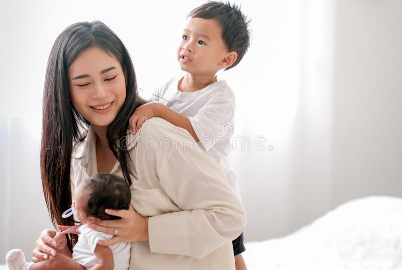 Soft blur image of beautiful Asian mother have fun with her little boy and newborn baby in front of day light stock photos