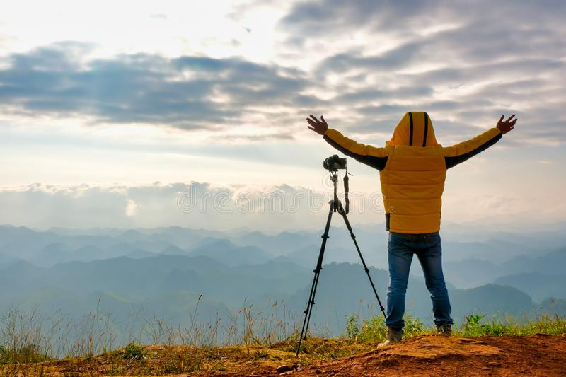 Soft blur image of the photographer with yellow jacket stand near to his camera and stand in front cliff, cloudy and show action. Of happy royalty free stock image