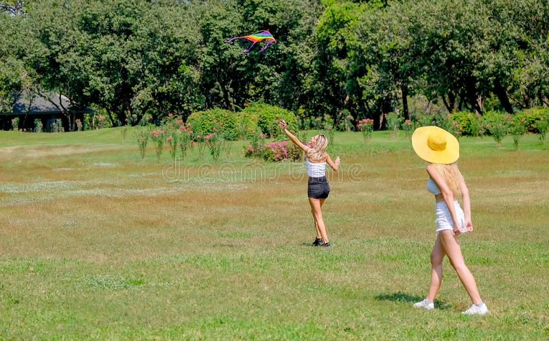 Soft blur of two teen girls play with kite in grass field of park or garden with day light stock images