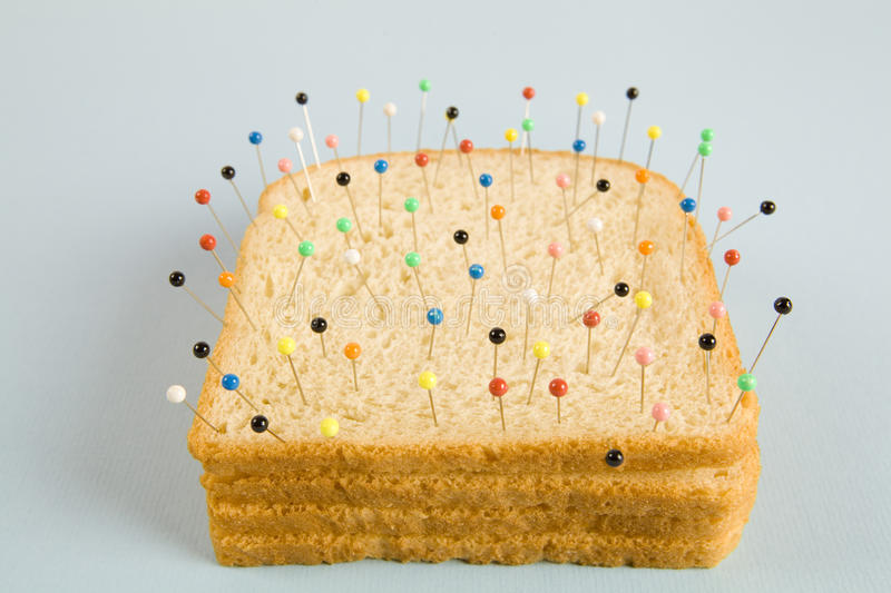 Soft bread voodoo. Still life photography of a quirky soft bread stacked and used as a voodoo doll on a blue and minimal background royalty free stock images
