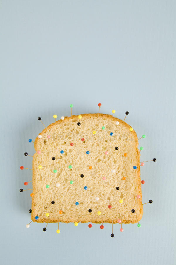 Soft bread voodoo. Still life photography of a quirky soft bread stacked and used as a voodoo doll on a blue and minimal background royalty free stock photo