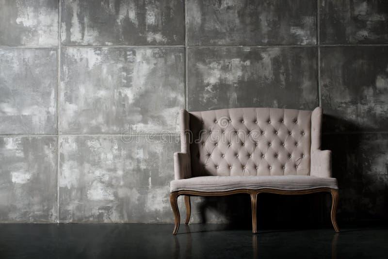 Soft chair. One soft chair on dark grey background, horizontal photo stock photo
