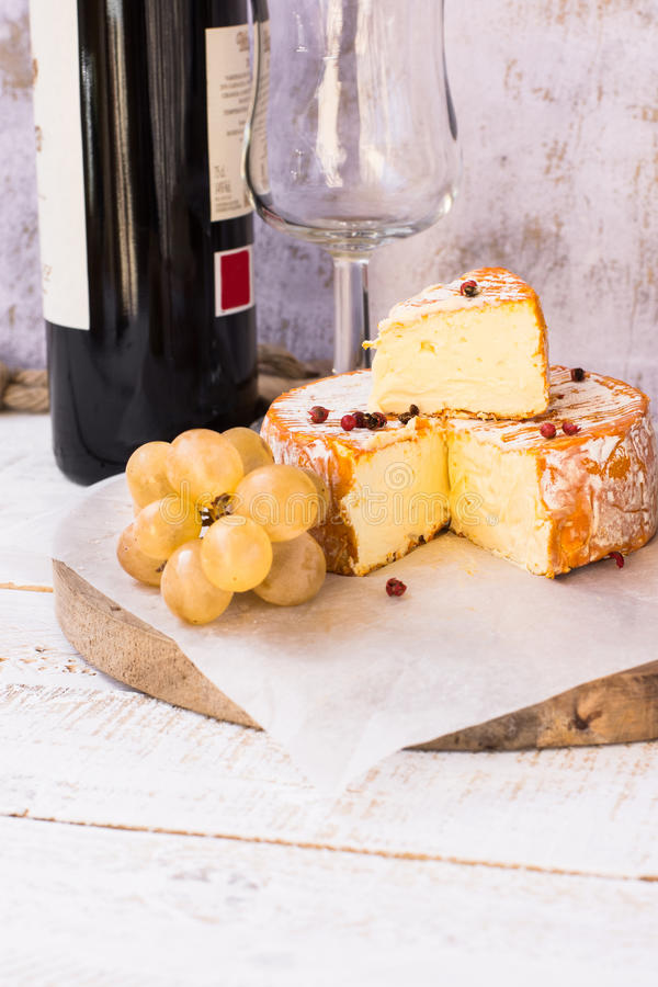 Soft cheese with cut off slice creamy texture, orange rind with mold, red pepper corns, grapes, wine bottle and glass stock photo