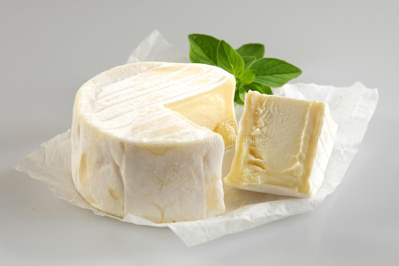 Soft Cheese with Cut Wedge and Fresh Basil stock image