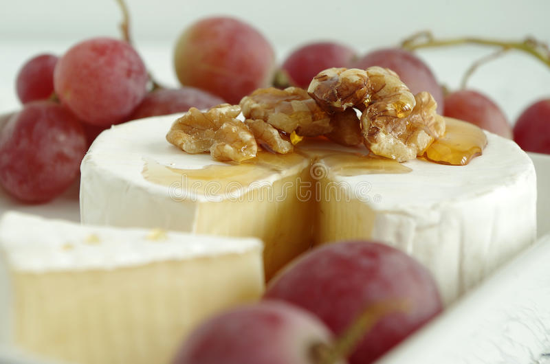 Soft cheese. French soft cheese with grapes royalty free stock photos