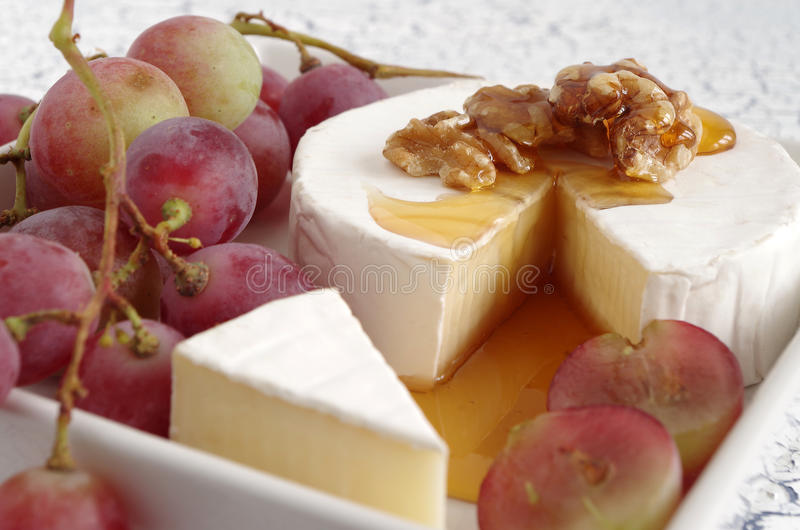 Soft cheese. French soft cheese with grapes stock photo