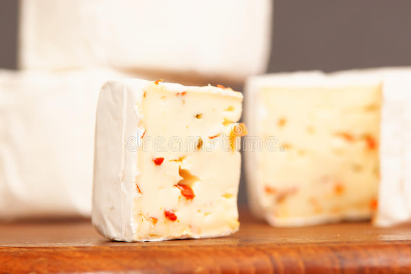 Soft cheese. On a wooden board with more cheeses in the background - very selective focus royalty free stock photography