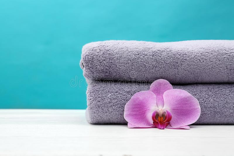 Soft clean towels with beautiful flower on table against color background. Space for text stock photography