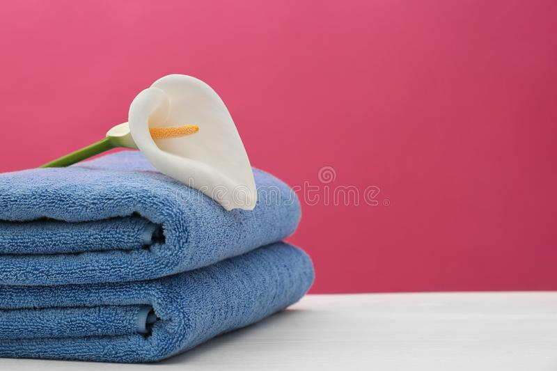 Soft clean towels with beautiful flower on table. Against color background. Space for text royalty free stock photography
