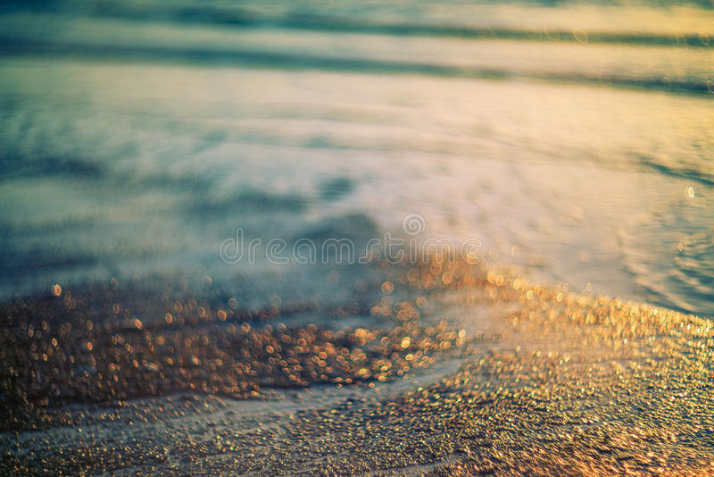 Soft color sand and water background. Soft color sand and water bokeh background at sunset stock photo