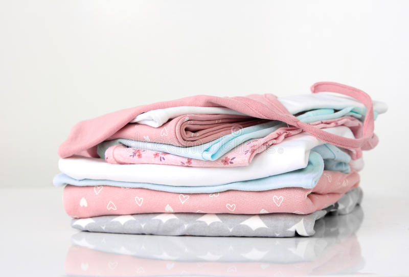 Soft color stack pile of clothes on white. Soft colors apparel.Stack cotton clothes on white stock photo