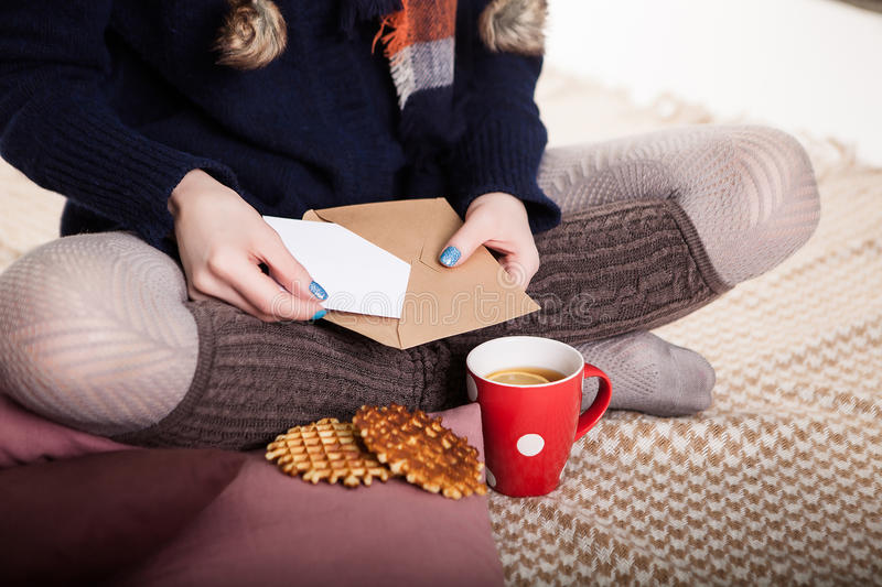 Soft cozy photo of slim tan woman in warm sweater on the bed with cup of tea in hands, top view point. Composition with stock photography