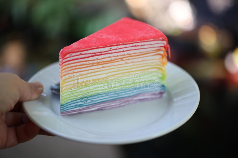 Soft crepe cake, beautiful color, blue, yellow, green, red, whipped cream and raspberry sauce Put plates and utensils.  stock images