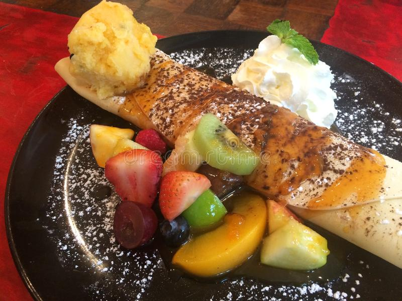 Soft crepes filling with mango and passion fruit sorbet icecream and icing serving with whip cream,fresh fruit strawberry raspberr stock photos