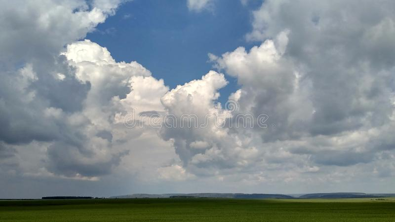 Soft cumulus clouds and green fields, summer landscape royalty free stock image