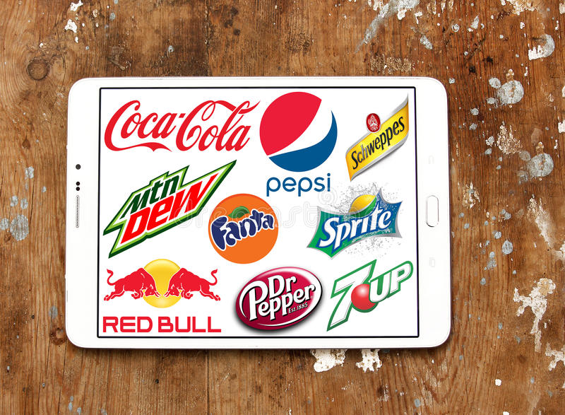 Soft drink brands and logos. Logos and brands of worldwide soft drinks manufacturers on white tablet on rusted wooden background. brands like pepsi , cocacola royalty free stock photos