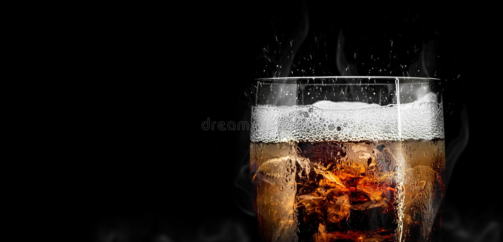 Soft drink glass with ice splash on cool smoke background. Cola glass with summer refreshment stock photos