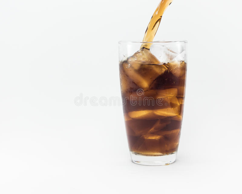 Soft drink pouring from a plastic bottle into a glass royalty free stock images