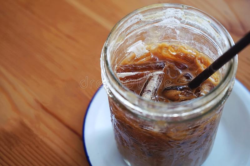 Summer refreshment drinks, glass of iced coffee with copy space placed on white plate and both placed on wooden table stock photo