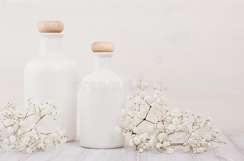 Soft elegant home decor with white bottles and small flowers on white wooden plank for advertising, designers, branding identity, royalty free stock image