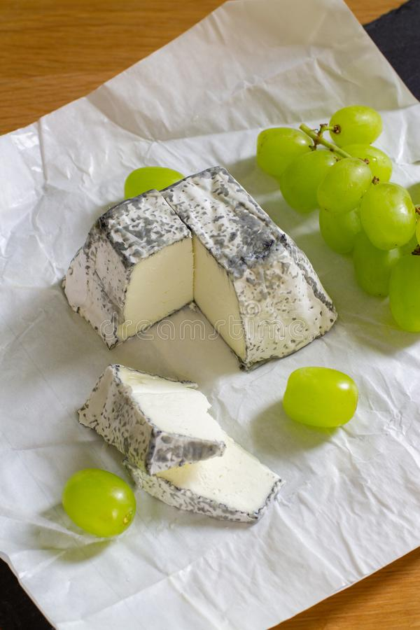 Soft farm cheese made from goat milk with mold and charcoal. Served with green grapes on white paper. A bar of soft cheese with royalty free stock photography