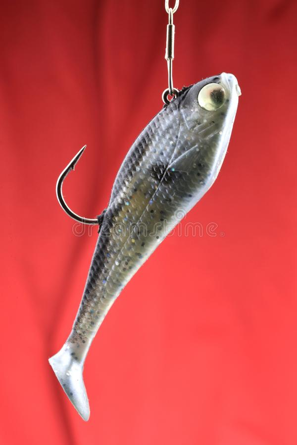 Soft Fish decoy. Artificial bait and hook on red background royalty free stock photo