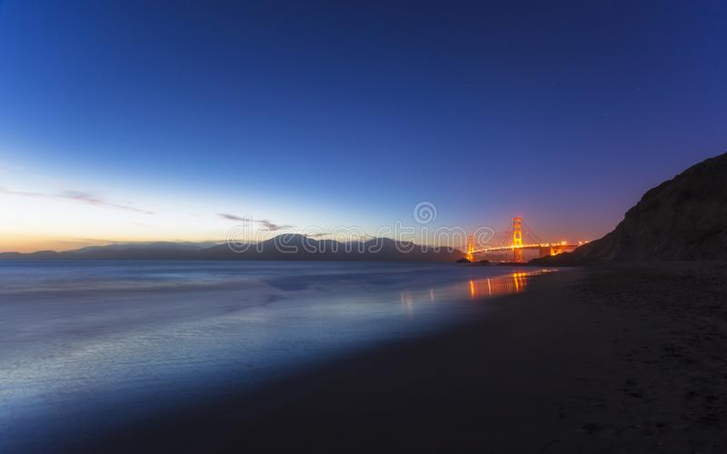 Soft flowing water reflects the beautiful Golden Gate Bridgefrom Baker beach, San Francisco royalty free stock photography