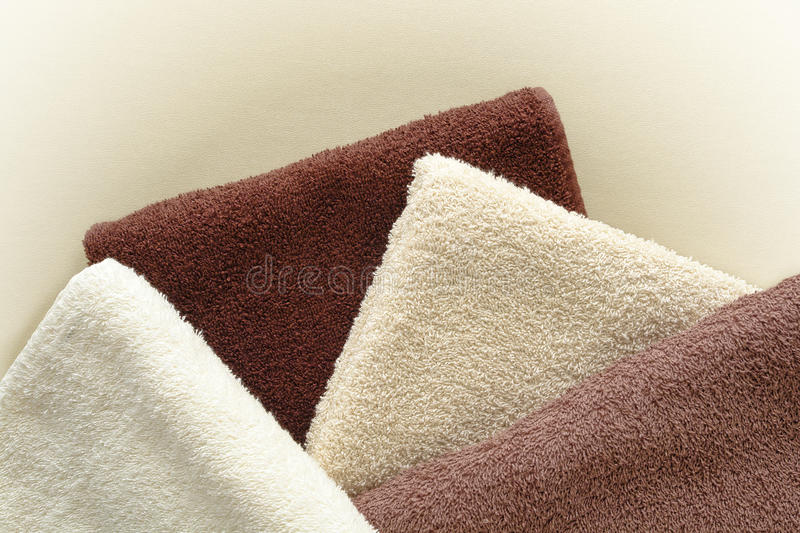 Soft and Fluffy Beige to Brown Cotton Bath Towels. Soft and fluffy cotton hotel quality bath towels in light beige to dark brown fashion colors over soft leather royalty free stock photo