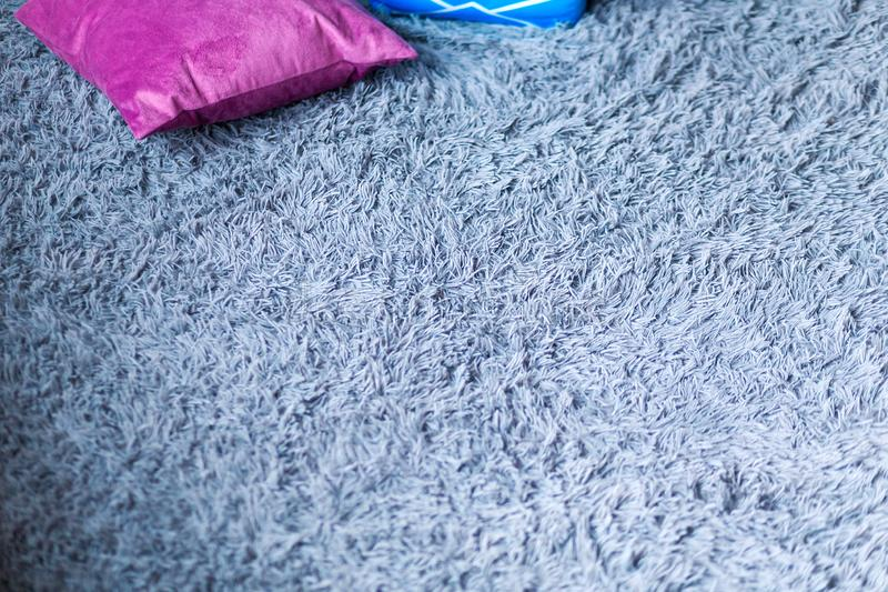 Soft fluffy gray carpet and purple pillows on it stock images
