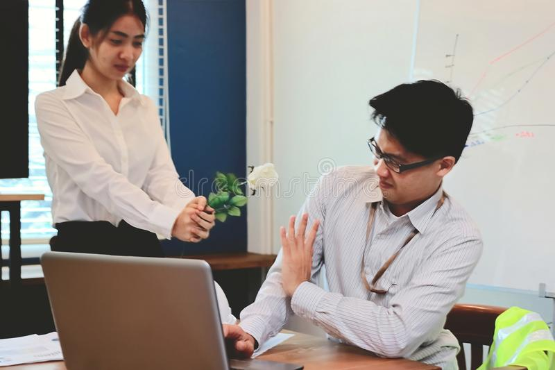 Soft focus angry Asian business man refuses a white roses from attractive woman. Vintage toned image. Soft focus angry Asian business men refuses a white roses royalty free stock image
