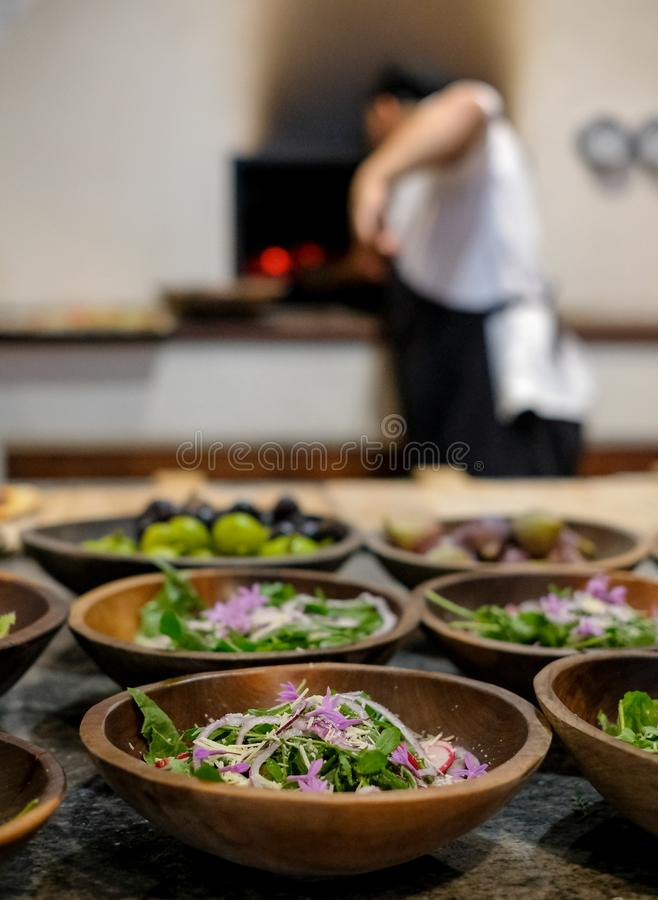 In soft focus in the background, chef puts pizza in pizza oven. In the foreground in focus, bowls of fresh salad. royalty free stock photos