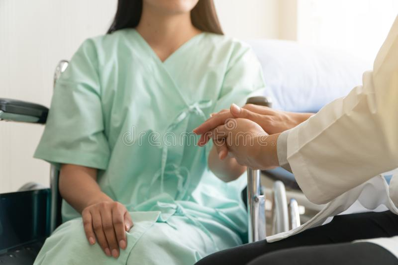Soft focus and blur of patient sitting in wheelchair in the hospital. And the doctor is holding the patient`s hand to encourage. stock images