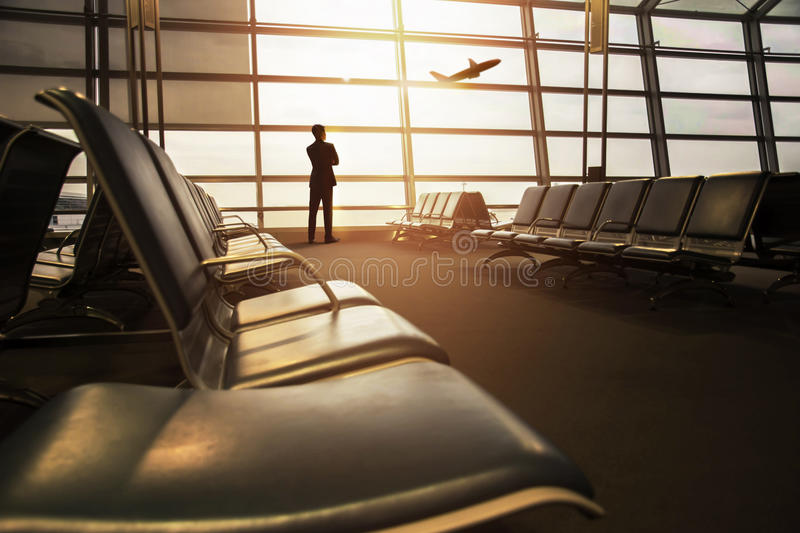 Soft Focus of Businessman in his Business Trip looking at Airplane Boarding in Airport Departures gate Terminal through royalty free stock photography