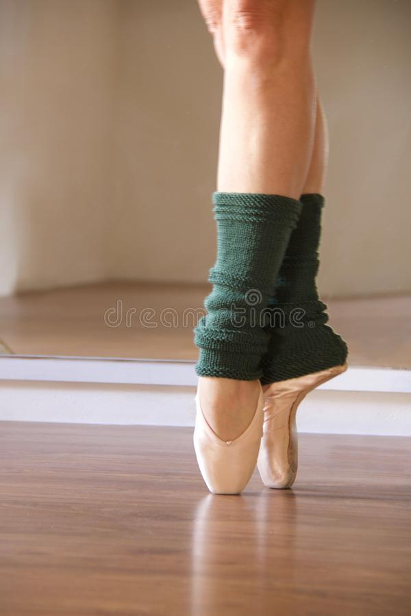 Soft focus on a feet of ballerina in pointe shoes. With green legwarmers royalty free stock photo