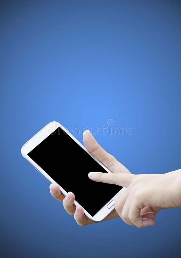 Soft focus at finger touch screen of cell phone. On dark blue background stock photo