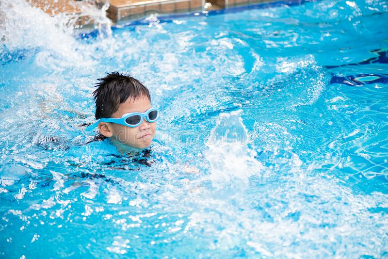 Soft focus on Happy young asian kid with swim goggles. Swimming in pool royalty free stock photo