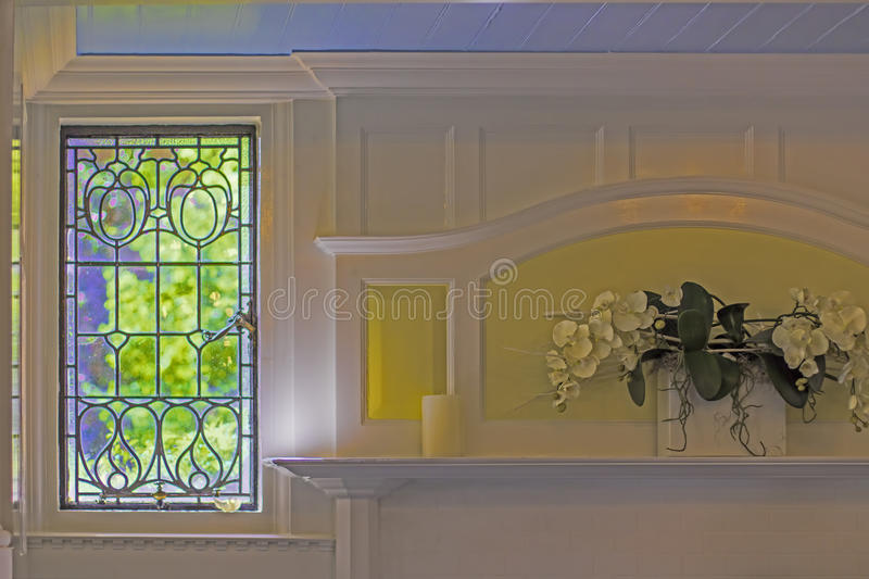 Soft focus pastel image of an English country cottage leaded win. Soft focus pastel image of an English country cottage window and white painted fireplace royalty free stock image